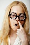 Junge blonde Jugendliche in den großen Gläsern täuschen herum und haben Spaßstudenten Lizenzfreie Stockfotografie