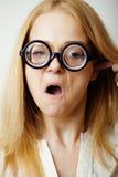 Junge blonde Jugendliche in den großen Gläsern täuschen herum und haben Spaßstudenten Stockfotografie