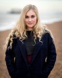 Junge blonde Jugendliche, die auf dem Strand denkt Stockfoto