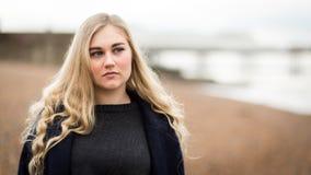 Junge blonde Jugendliche, die auf dem Strand denkt Stockfotografie