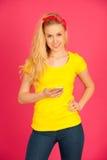 Junge blonde Jugendliche im gelben T-Shirt, welches das Netz auf Inspektion surft Stockfotografie