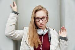 Junge blonde kühle Frau auf einer Wand Stockfotografie