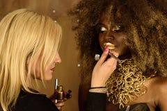 Junge blonde Künstlermalerei-Goldlippen mit Quaste, arbeiten das afrikanische oder schwarze amerikanische Modell um, das helles M Stockfoto