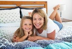 Junge blonde kaukasische Frau, die auf Bett zusammen mit ihren Jungen liegt Lizenzfreies Stockfoto