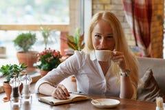 Junge blonde kaukasische Frau mit glücklichem Lächeln trinkt Kaffee Stockbilder