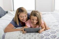 Junge blonde kaukasische Mutter, die auf Bett mit ihrem jungen Bonbon 7 Jahre alte Tochter verwenden Internet auf digitaler Inter Stockbild