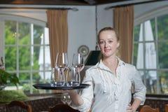 Junge blonde Kellnerin in einem Restaurant Lizenzfreie Stockbilder