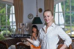 Junge blonde Kellnerin in einem Restaurant Stockbilder