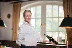 Junge blonde Kellnerin in einem Restaurant Stockfoto