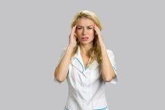 Junge blonde Krankenschwester, die Kopfschmerzen hat Lizenzfreie Stockbilder