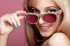 Junge blonde lächelnde Frau mit Spaßsüßigkeitsgläsern auf rosa backg Stockfoto