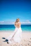 Junge blonde lange Haarbraut im langen weißen Kleid mit dem offenen Rücken, der auf dem weißen Sandstrand steht Stockfoto