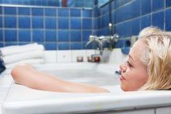 Junge blonde lächelnde Frauen in der Badewanne Stockfotografie