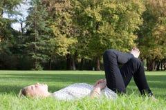 Junge blonde Mädchenlauge auf Gras entspannen sich Zeit und nette Frau Stockfoto