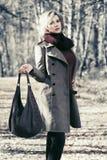 Junge blonde Modefrau, die in Herbstwald geht Lizenzfreies Stockbild