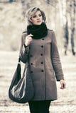 Junge blonde Modefrau, die in Herbstwald geht Lizenzfreie Stockfotografie