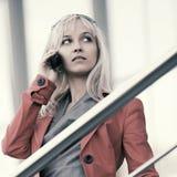 Junge blonde Modefrau, die um den Handy im Freien ersucht Stockbilder