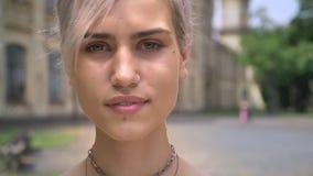 Junge blonde moderne Frau mit durchbohrter Nase und kurzen dem Haarschnitt, welche die Kamera, durchdacht betrachtet stock footage