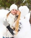 Junge blonde Mutter, die draußen ihre kleine Tochter küsst Lizenzfreies Stockfoto