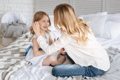 Junge blonde Mutter, die ihr Tochterhaar berührt Lizenzfreie Stockfotografie