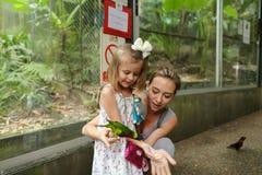 Junge blonde Mutter und kleine Tochter, die mit Papageien draußen in Thailand genießt Lizenzfreie Stockfotos