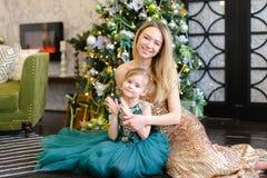 Junge blonde Mutter und kleine Tochter mit Bengal-Licht, das auf Boden nahe Weihnachtsbaum sitzt Stockfotos