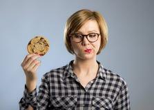 Junge blonde nette und freundliche kaukasische Frau in der zufälligen Kleidung, die großes köstliches Schokoladenplätzchen hält Stockfotos