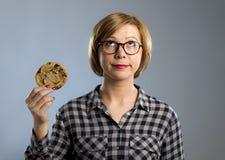 Junge blonde nette und freundliche kaukasische Frau in der zufälligen Kleidung, die großes köstliches Schokoladenplätzchen hält Lizenzfreie Stockfotos