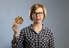 Junge blonde nette und freundliche kaukasische Frau in der zufälligen Kleidung, die großes köstliches Schokoladenplätzchen hält Lizenzfreies Stockbild