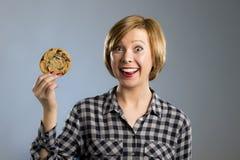 Junge blonde nette und freundliche kaukasische Frau in der zufälligen Kleidung, die großes köstliches Schokoladenplätzchen hält Stockfoto