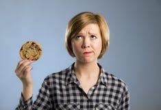 Junge blonde nette und freundliche kaukasische Frau in der zufälligen Kleidung, die großes köstliches Schokoladenplätzchen hält Lizenzfreie Stockfotografie