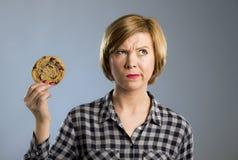 Junge blonde nette und freundliche kaukasische Frau in der zufälligen Kleidung, die großes köstliches Schokoladenplätzchen hält Stockbilder