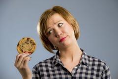Junge blonde nette und freundliche kaukasische Frau in der zufälligen Kleidung, die großes köstliches Schokoladenplätzchen hält Stockbild