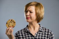Junge blonde nette und freundliche kaukasische Frau in der zufälligen Kleidung, die großes köstliches Schokoladenplätzchen hält Lizenzfreie Stockbilder