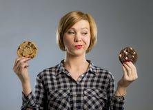 Junge blonde nette und freundliche kaukasische Frau in der zufälligen Kleidung, die zwei große Schokoladenplätzchen hält Stockfoto