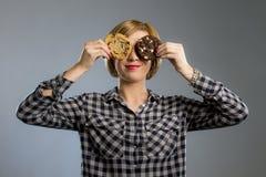 Junge blonde nette und freundliche kaukasische Frau in der zufälligen Kleidung, die zwei große Schokoladenplätzchen hält Lizenzfreie Stockfotos
