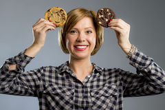Junge blonde nette und freundliche kaukasische Frau in der zufälligen Kleidung, die zwei große Schokoladenplätzchen hält Lizenzfreie Stockfotografie