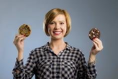 Junge blonde nette und freundliche kaukasische Frau in der zufälligen Kleidung, die zwei große Schokoladenplätzchen hält Lizenzfreies Stockfoto