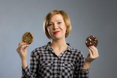 Junge blonde nette und freundliche kaukasische Frau in der zufälligen Kleidung, die zwei große Schokoladenplätzchen hält Stockbilder