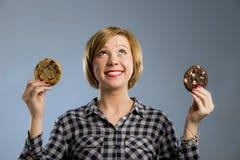 Junge blonde nette und freundliche kaukasische Frau in der zufälligen Kleidung, die zwei große Schokoladenplätzchen hält Stockbild