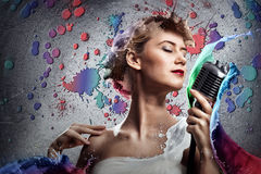 Junge blonde Sängerin mit Mikrofon Lizenzfreie Stockbilder