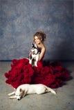 Junge blonde schöne junge Frau, die Schlittenhundhündchen umarmt Stockbilder