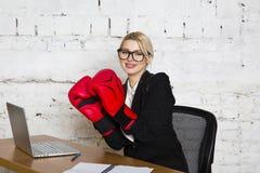 Junge blonde Schönheitsgeschäftsfrau, die an einem Bürotisch mit Laptop, Notizbuch und Gläsern in der Klage und in den Boxhandsch Stockfotografie