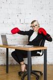 Junge blonde Schönheitsgeschäftsfrau, die an einem Bürotisch mit Laptop, Notizbuch und Gläsern in der Klage und in den Boxhandsch Stockbild
