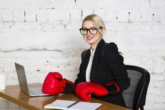 Junge blonde Schönheitsgeschäftsfrau, die an einem Bürotisch mit Laptop, Notizbuch und Gläsern in der Klage und in den Boxhandsch Stockfoto
