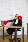 Junge blonde Schönheitsgeschäftsfrau, die an einem Bürotisch mit Laptop, Notizbuch und Gläsern in der Klage und in den Boxhandsch Lizenzfreies Stockfoto