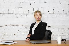 Junge blonde Schönheitsgeschäftsfrau, die an einem Bürotisch mit Laptop, Notizbuch und Gläsern in der Klage sitzt Die goldene Tas Lizenzfreies Stockfoto