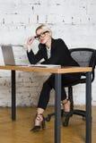 Junge blonde Schönheitsgeschäftsfrau, die an einem Bürotisch mit Laptop, Notizbuch und Gläsern in der Klage sitzt Die goldene Tas Stockfotografie