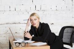 Junge blonde Schönheitsgeschäftsfrau, die an einem Bürotisch mit Laptop, Notizbuch und Gläsern in der Klage sitzt Die goldene Tas Stockbild