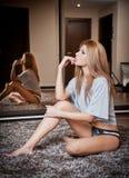Junge blonde sinnliche Frau, die auf dem Bodendenken sitzt. Schönes junges Mädchen mit der bequemen Kleidung, die auf dem Teppich  Stockfotografie